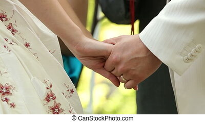 Holding hands - Bride and fiance holding hands during the...