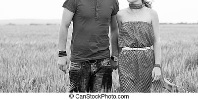 Holding hands couple on green field black and white