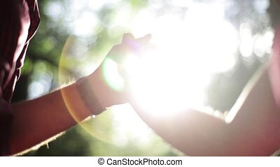 Holding hands of in love couple in green summer forest. Sun beams.