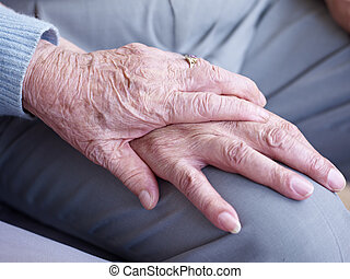 holding hands - hand of an elderly woman holding the hand of...