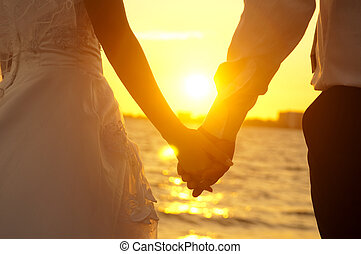 Holding Hands - Young adult male groom and female bride...