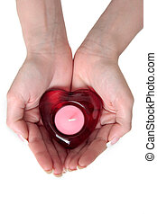 Holding heart in hands - womans hands holding a heart candle...