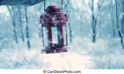 Holding in red glove red candle lantern in the winter forest.