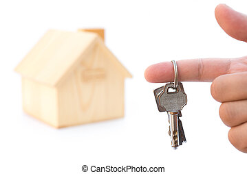 holding keys in front of a house model on white