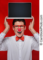 Holding laptop on his head. Cheerful man with clown holding a laptop on his head while standing isolated on red