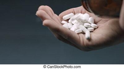 Holding many white drug pills