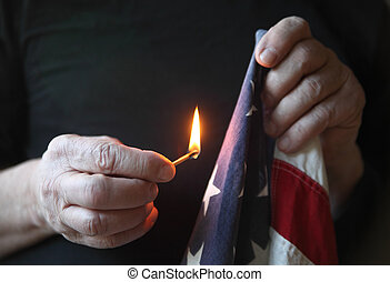 holding match to American flag