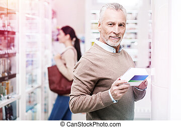 Hoary purchaser smiling and holding a medication