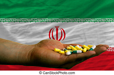 holding pills in hand in front of iran national flag