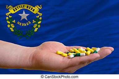 man holding capsules in front of complete wavy american state flag of nevada symbolizing health, medicine, cure, vitamines and healthy life