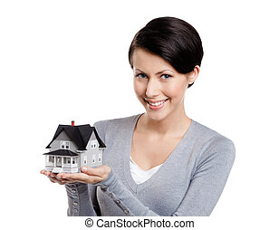 Holding small toy house - Young woman hands small toy house,...