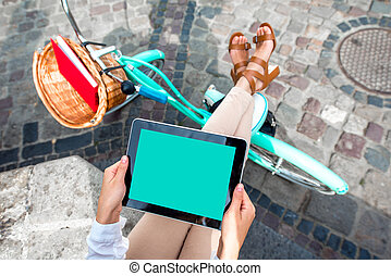 Holding tablet in the hands with bicycle on background in the city