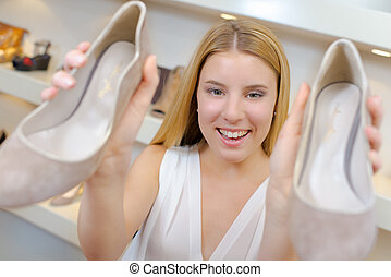Holding up a pair of shoes