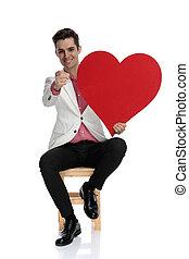holdingen, hjärta, pekar, finger, elegant, man, röd, lycklig, sittande