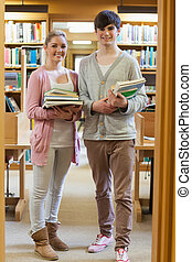 holdingen, par, stående, böcker, bibliotek