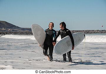 holdingen, par, ung, surfarear, svart, en annan, räcker, le, en, wetsuits, lycklig