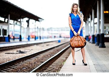 holdning, dame, venter, tog, på, den, platform, i, jernbane station
