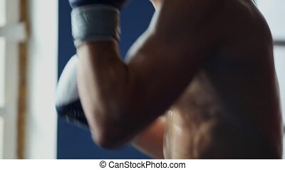 Holds a professional boxer shadow Boxing wearing Boxing gloves with his shirt off. A vertical camera movement in close-up. Pan.