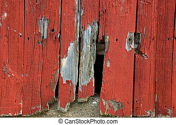 hole in barn siding - Jagged hole in red barn siding.