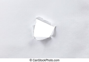 Hole in the sheet of white paper with torn sides.