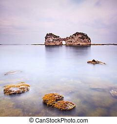 Hole island and rocks in a tropical blue ocean. Cloudy sky....