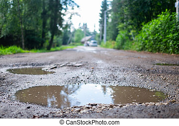 Holes and pothole on a rural road after rain in spring