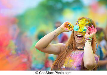 Young cheerful woman at Holi paint party