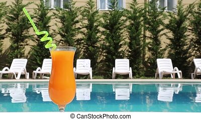 Holiday - A glass of juice standing near the swimming pool.