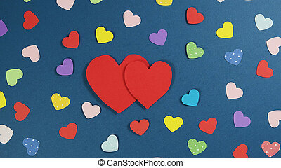 Holiday Abstract Valentine Background with multicolored paper Hearts. Cutted paper heart on blue background