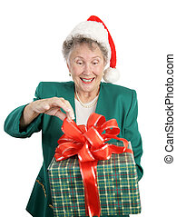 A senior woman anticipating opening a big Christmas gift. Isolated on white.