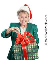 Holiday Anticipation - A senior woman anticipating opening a...