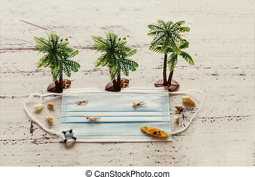 Holiday at the beach during a pandemic, face mask with miniature figures, pandemic holiday concept