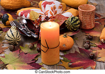 Holiday candle glowing for dinner setting for fall season with real gourd decorations and leaves