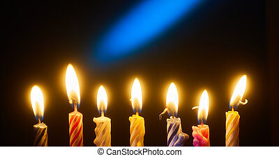 Holiday candles in a row on dark background