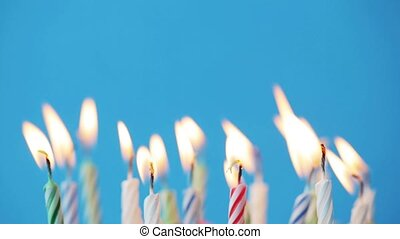 birthday candles burning over blue background