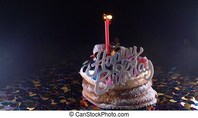 holiday, celebration and party concept - birthday cupcake with one burning candles over black background, confetti. Confetti for a party. super slow motion