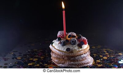 holiday, celebration and party concept - birthday cupcake with one burning candles over black background, confetti. Confetti for a party. 4k, slow motion