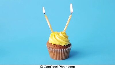birthday cupcake with two burning candles