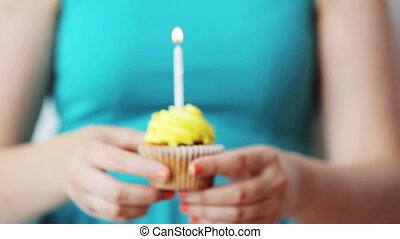 woman with burning candle on birthday cupcake