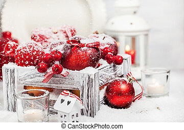 Christmas composition with red apples, balls, cinnamon, snow and candles