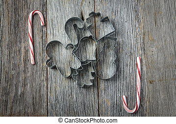 Holiday Cookie Cutters and Candy Cane on Rustic Wood Background