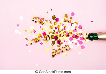 Holiday creative concept. Christmas composition with champagne bottle golden sparkles on pastel pink background