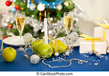 Image of holiday table with flutes of champagne, fruits, gifts, candle and plates on it