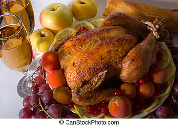 Roasted chicken or turkey garnished with lemon, cranberry, apples, tomatoes, bread and wine.