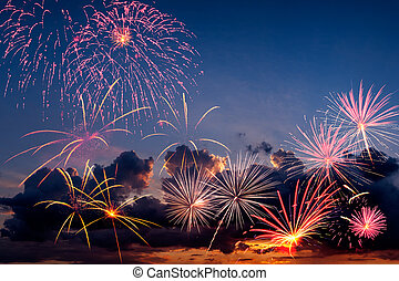 Holiday fireworks in the evening sky with majestic clouds, ...