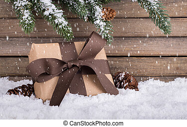 Brown holiday gift box on snowand snow falling with a rustic wooden background