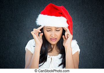 Closeup portrait, young beautiful worried stressed wife, mother, woman in santa claus hat with hands on temples looking down, isolated gray black background. Last minute christmas shopping