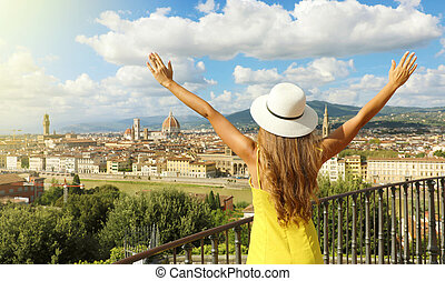 Holiday in Italy. Panoramic back view of young woman with hat and raised arms looking at Florence city, Tuscany, Italy.
