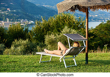 Holiday on a lake - Young woman lying in a deck chair with a...
