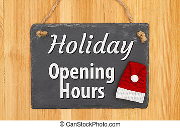 Holiday Opening Hours type message on hanging chalkboard sign with a Santa hat